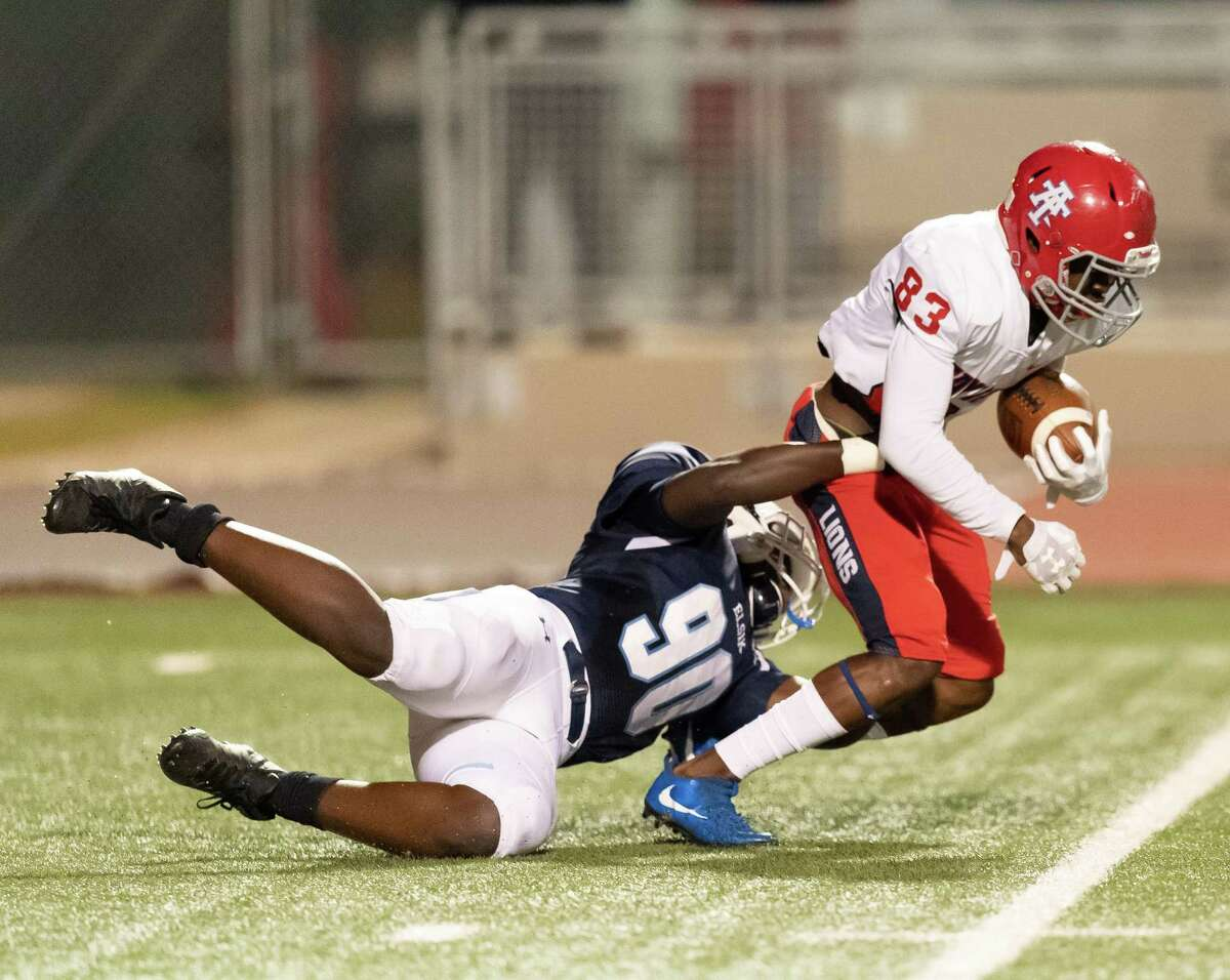 Khalid Balogun (83) of the Alief Taylor Lions is brought down behind the line of scrimmage in the first half by David Mubalama (90) of the Alief Elsik Rams during a High School football game on Friday, October 16, 2020 at Crump Stadium in Houston Texas.