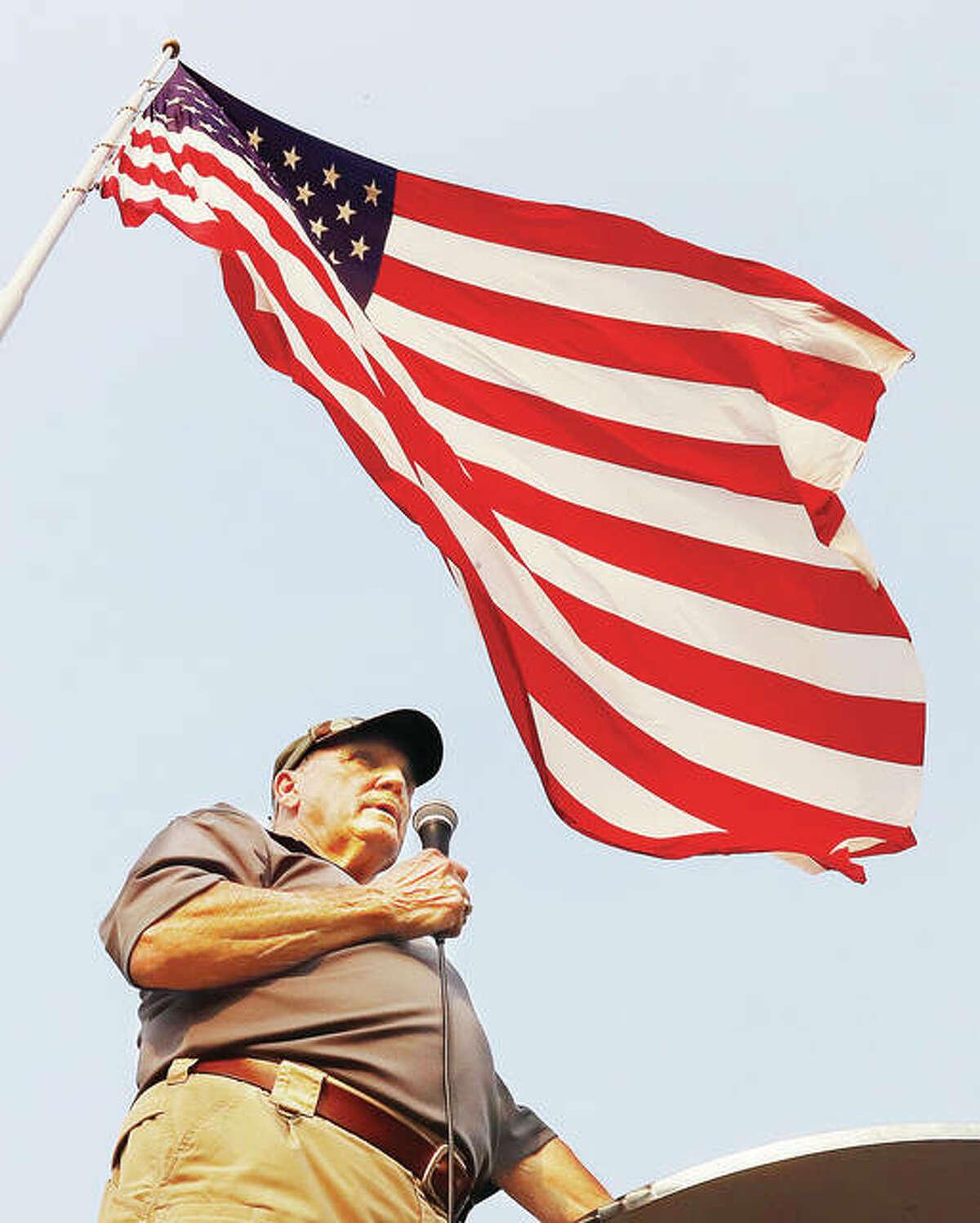Terry Day, chairman of the veterans committee in Grafton, speaks to a crowd of about 100 people who gathered near the lage American flag on the riverfront in Grafton Saturday.