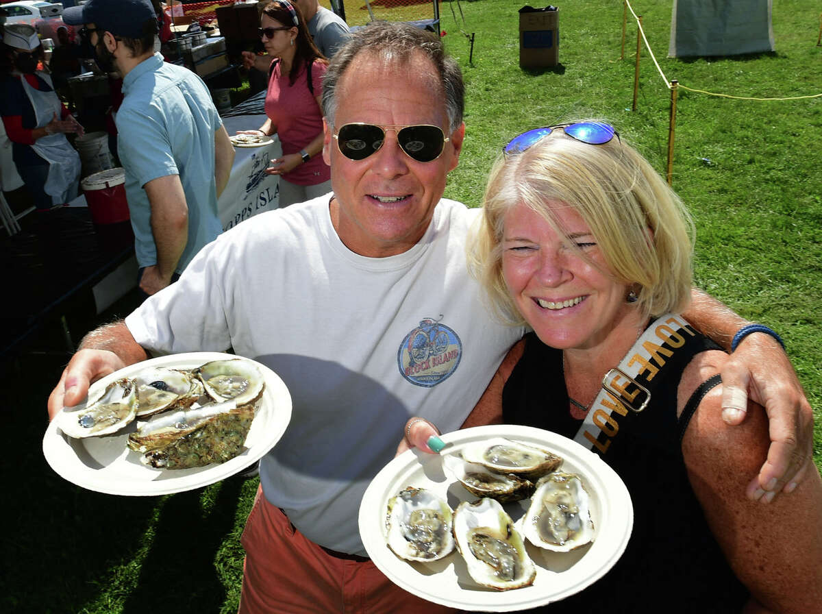 Doug Garaofalo of Stamford and Mary Beth Montague of Greenwich enjoy oysters from the Coast Guard Auxiliary booth during the 43rd Annual Norwalk Oyster Festival Saturday, September 11, 2021, at Veterans Memorial Park in Norwalk, Conn.