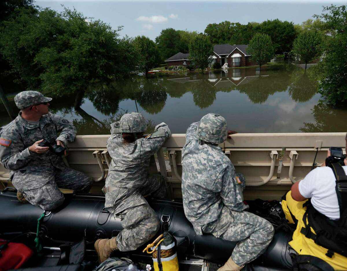 Members of the Texas Army National Guard and Texas Task Force 1, look at the flood damage in a Brookshire neighborhood, from a truck, as they and Waller County Sheriffs office, and Waller County Judge Trey Duhon, with Waller County Commissioner Justin Beckendorff, Tuesday, April 19, 2016. ( Karen Warren / Houston Chronicle )