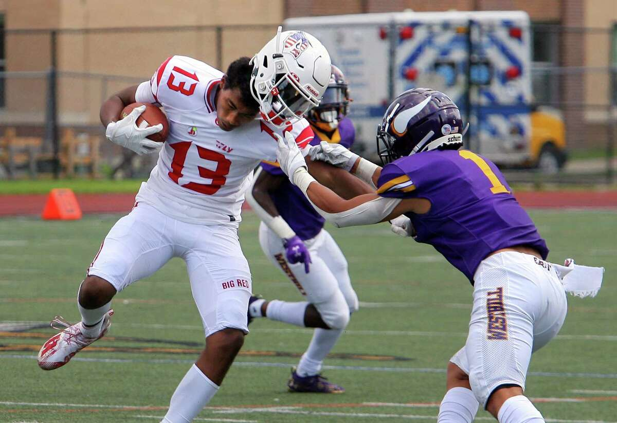 Greenwich's Chason Barber (13) helmet comes off as he's tackled by Westhill's Kevin Laba in Stamford on Saturday.