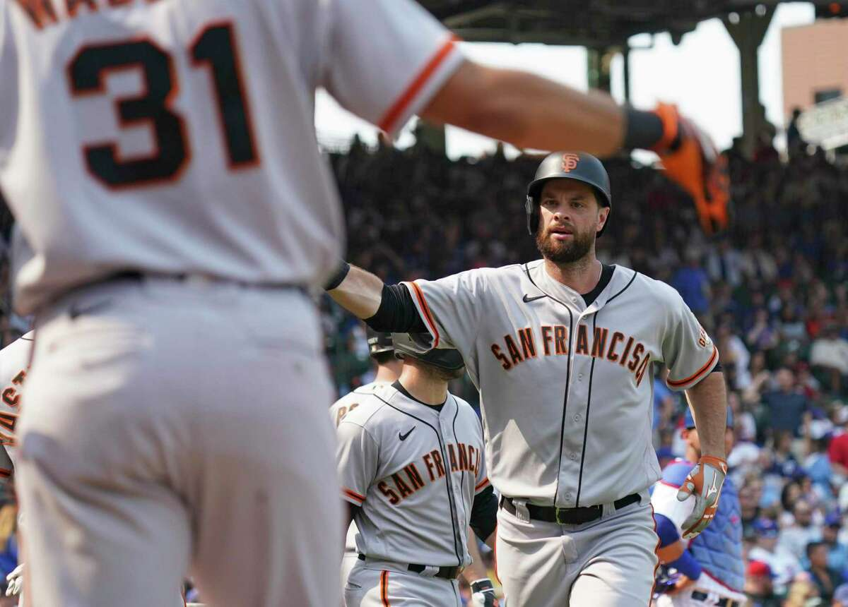 CHICAGO, ILLINOIS - SEPTEMBER 11: Brandon Belt #9 of the San Francisco Giants is congratulated by teammates following his three-run home run during the second inning of a game against the Chicago Cubs at Wrigley Field on September 11, 2021 in Chicago, Illinois. (Photo by Nuccio DiNuzzo/Getty Images)