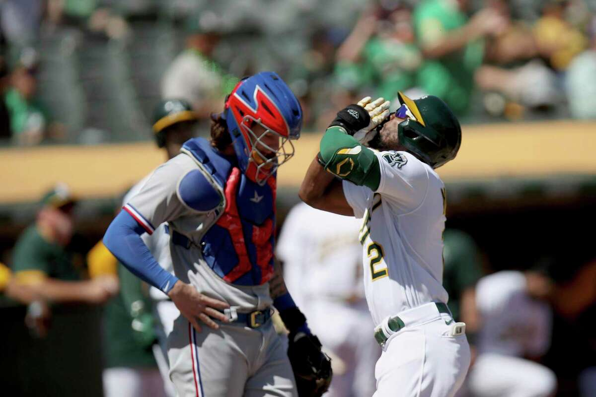 Oakland Athletics' Starling Marte (2) crosses home plate in front of Texas Rangers catcher Jonah Heim (28) after hitting a solo home run in the first inning of a baseball game Saturday, Sept. 11, 2021, in Oakland. (AP Photo/Scot Tucker)