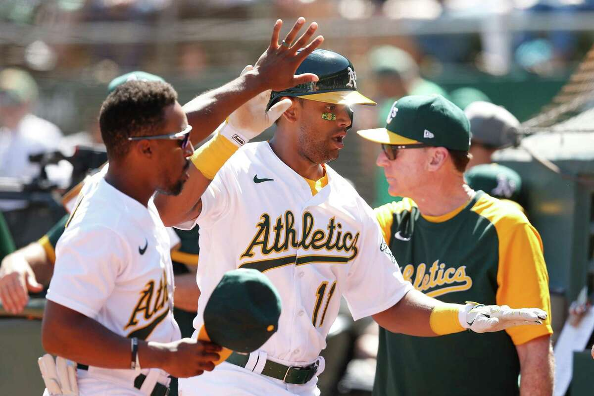 OAKLAND, CALIFORNIA - SEPTEMBER 11: Khris Davis #11 of the Oakland Athletics celebrates with Tony Kemp #5 and manager Bob Melvin #6 after scoring on a single by Chad Pinder #4 in the bottom of the second inning against the Texas Rangers at RingCentral Coliseum on September 11, 2021 in Oakland, California. (Photo by Lachlan Cunningham/Getty Images)