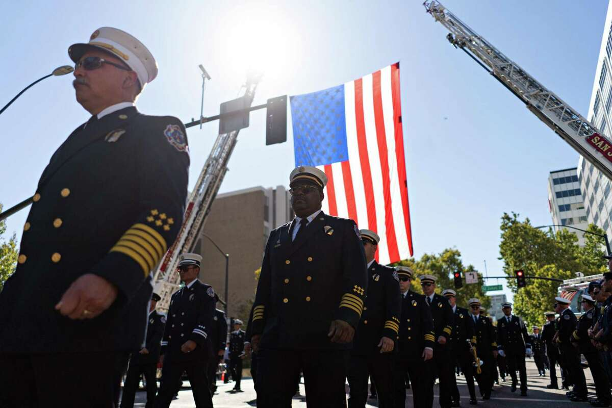 Firefighters from San Jose and surrounding jurisdictions end their procession under a large American flag suspended overheard during the 2021 Patriot Day Procession in San Jose.
