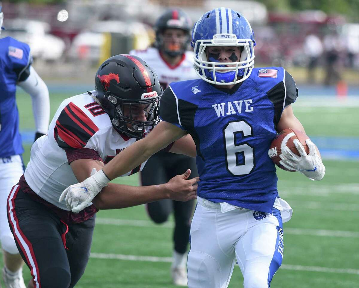 Darien's Matt Minicus scores on a 33-yard touchdown pass from Miles Drake as Warde's Anwar Sakly pursues on Saturday.