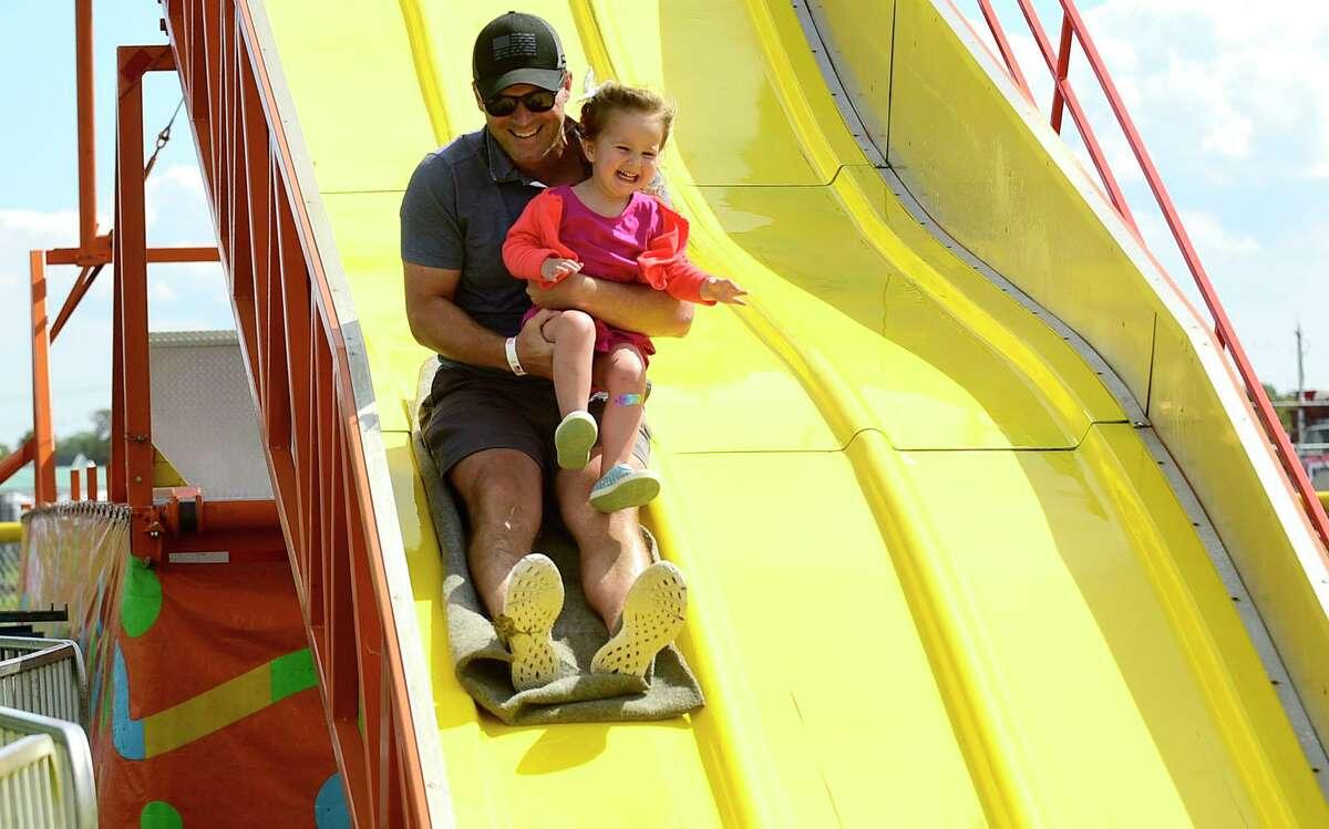Chris McIntyre and his daughter Eva, 2, go down the giant slide at the 43rd Annual Norwalk Oyster Festival Saturday, September 11, 2021, at Veterans Memorial Park in Norwalk, Conn.