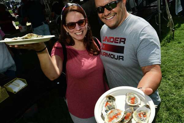 Jenny Melendez and Martin Cabassa enjoy oysters from the Coast GUard Auxiallry booth during the 43rd Annual Norwalk Oyster Festival Saturday, September 11, 2021, at Veterans Memorial Park in Norwalk, Conn.