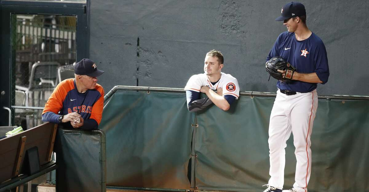 Houston Astros pitcher Zach Greinke throws a bullpen session with pitching coach Brent Strom and Jake Odorizzi watching during batting practice before the start of an MLB baseball game at Minute Maid Park, Friday, September 10, 2021, in Houston.