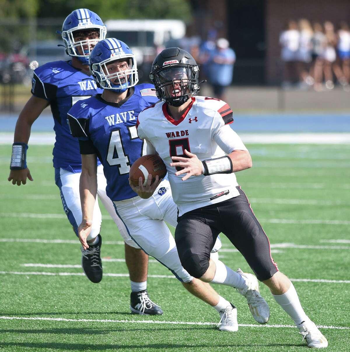 Warde quarterback Charles Gulbin runs for some yards as Darien's Mason Hedley pursues on Saturday.