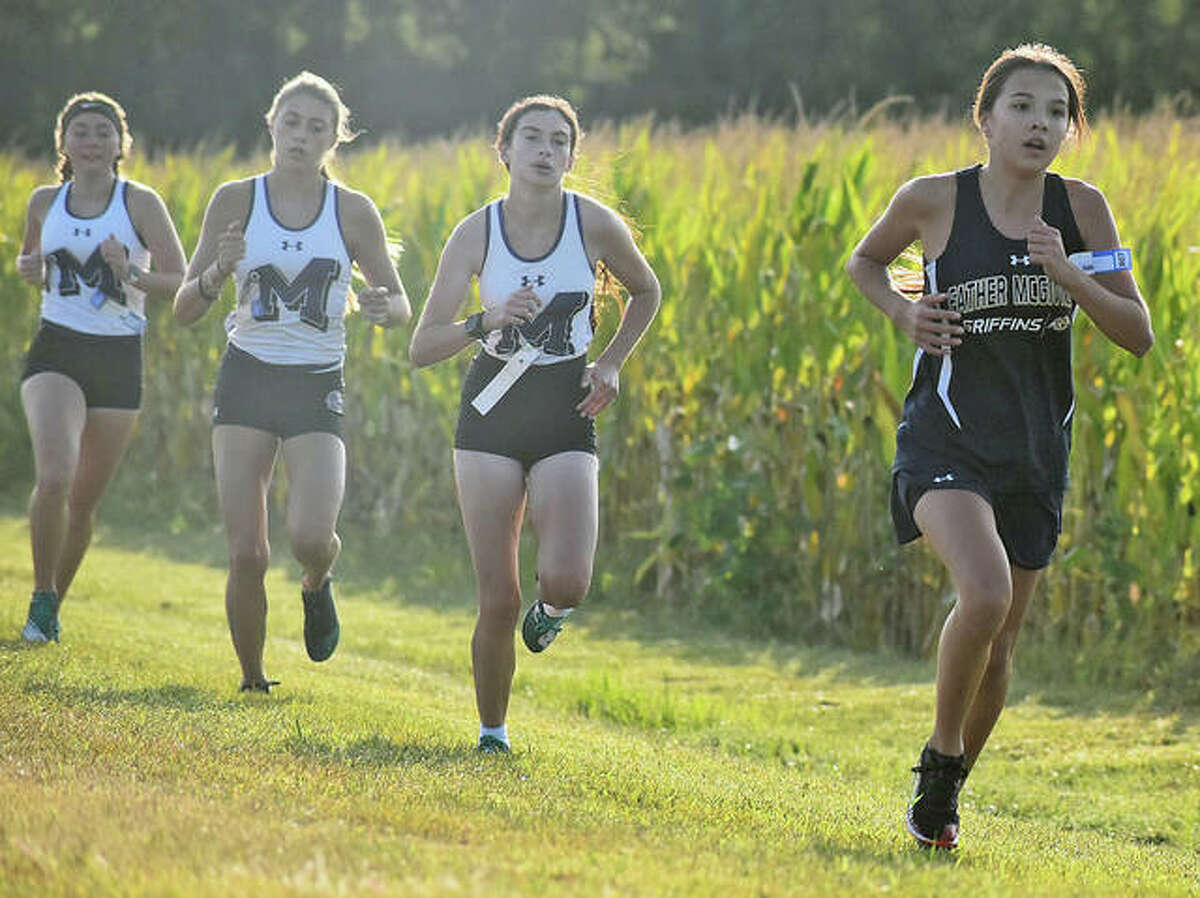 Father McGivney's Kaitlyn Hatley breaks out in front of a pack of Mascoutah runners on the home stretch last year.