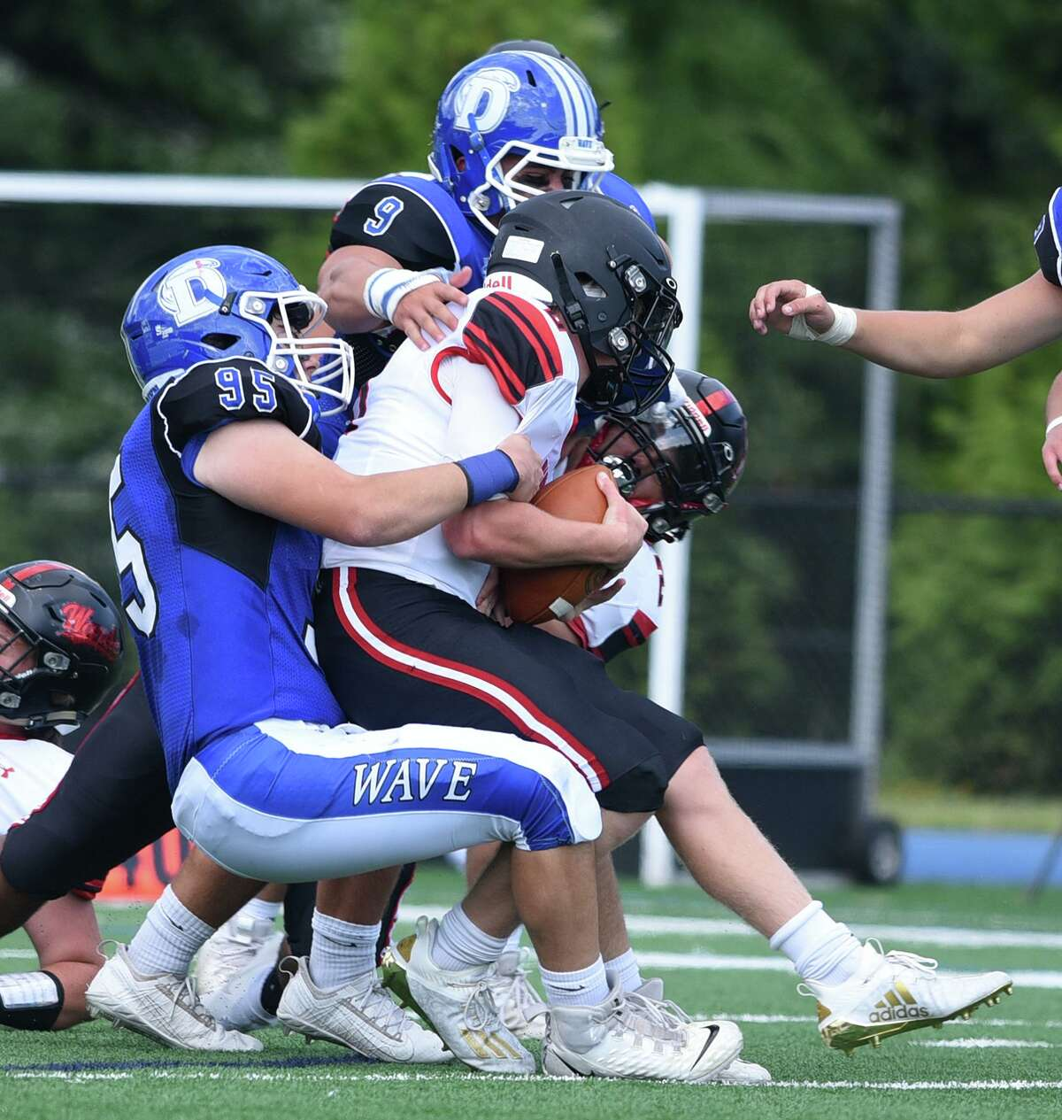 Darien's Kyle Santos (95) and David Evanchick (9) wrap up Warde's Charles Gulbin (8) during a football game at Darien High School on Sat., Sept. 11, 2021.