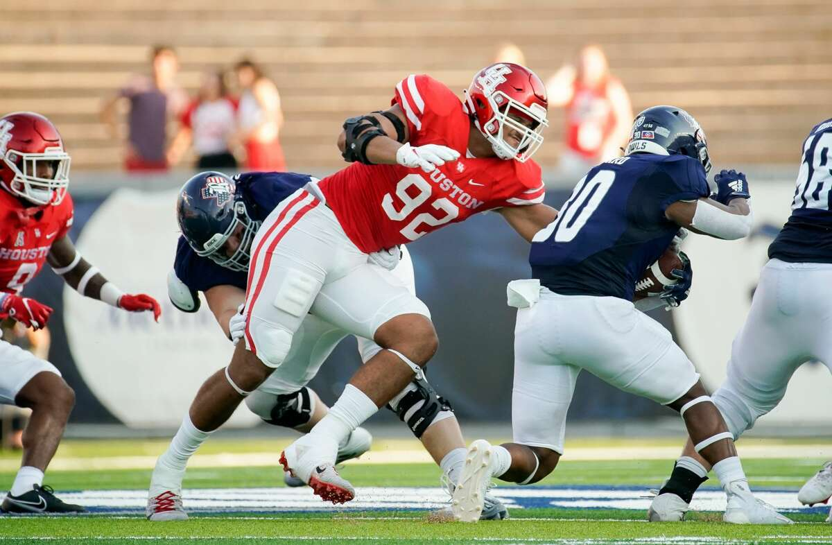 Houston Cougars defensive lineman Logan Hall (92) tackles Rice Owls running back Ari Broussard (30) during the first quarter of an NCAA game at Rice Stadium on Saturday, Sept. 11, 2021, in Houston.