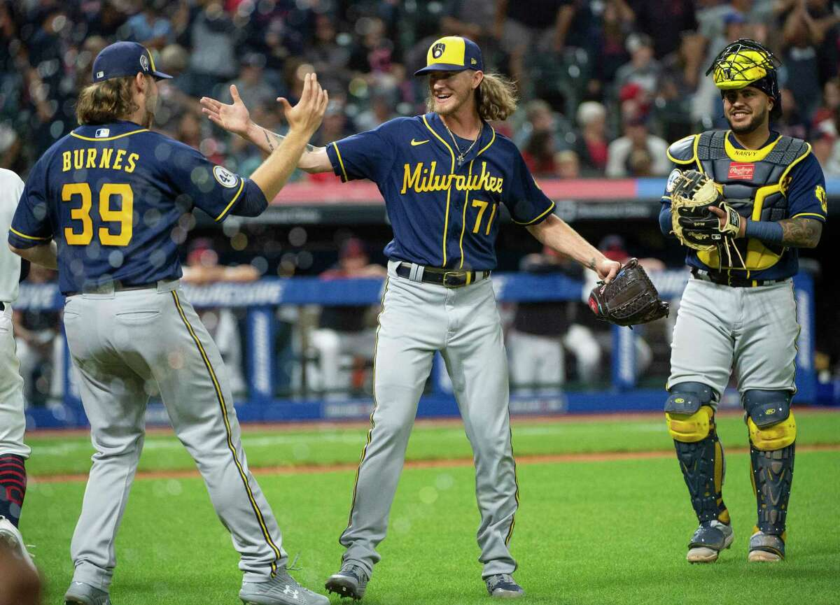 Milwaukee Brewers starting pitcher Corbin Burnes (39) greets relief pitcher Josh Hader as Omar Narvaez watches at the end of a baseball game against the Cleveland Indians in Cleveland, Saturday, Sept. 11, 2021. Hader and Burnes combined for a no-hitter.
