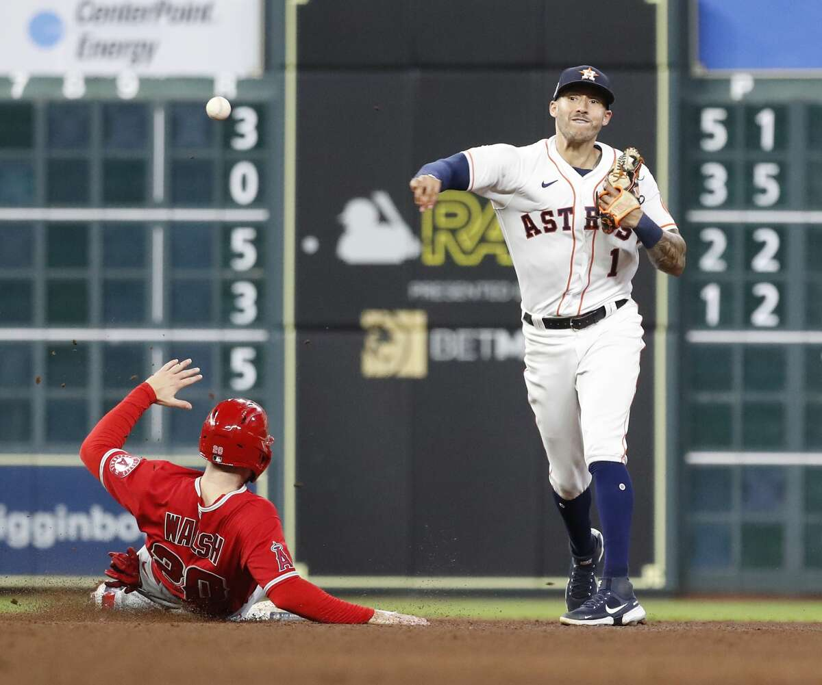 Houston Astros shortstop Carlos Correa (1) makes the throw to first base after tagging Los Angeles AngelsJared Walsh (20) as Brandon Marsh ground into a double play during the fifth inning of a MLB baseball game at Minute Maid Park, Saturday, September 11, 2021, in Houston.