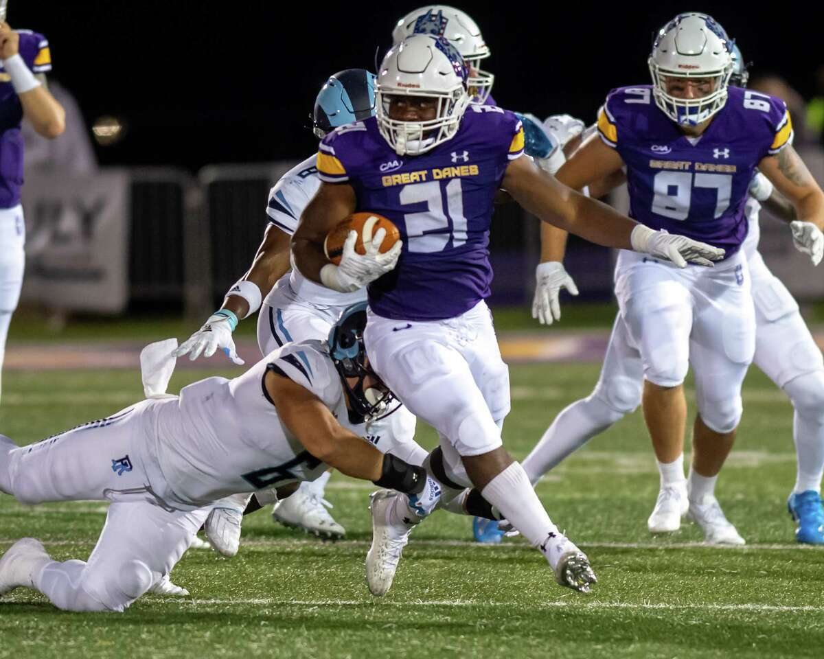 UAlbany running back Karl Mofor, shown picking up yardage in front of Rhode Island defender Evan Stewart during the Great Danes' home opener on Sept. 11, 2021, said he's willing to do whatever it takes to get the Danes on track.