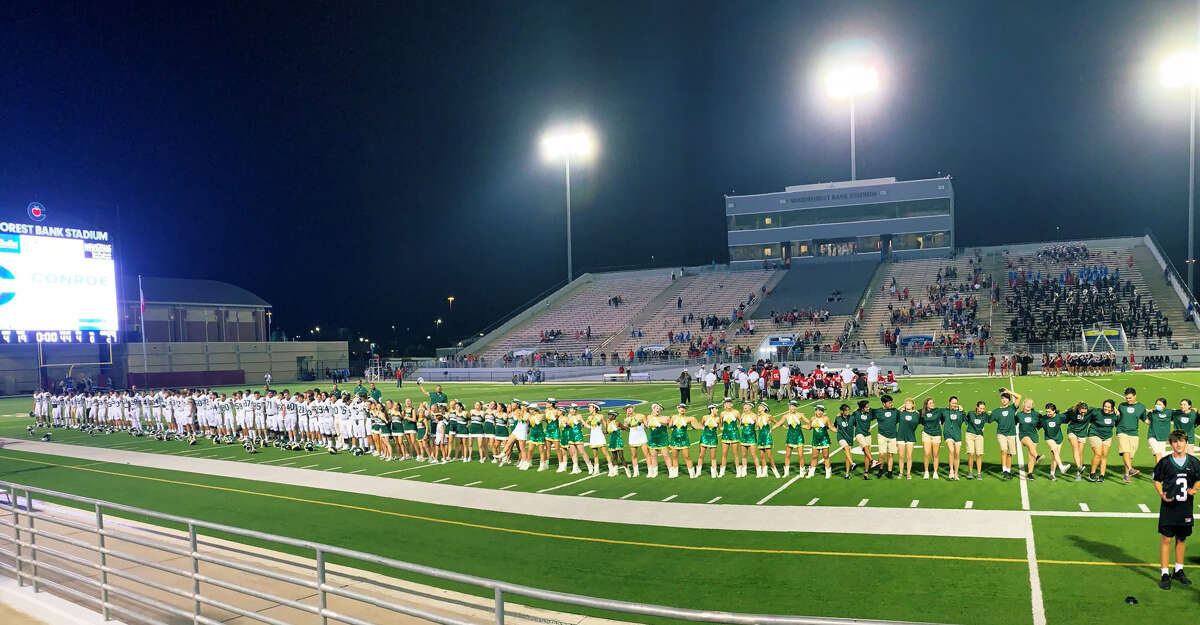 The Stratford football players, cheerleaders, Spartanaires and trainers sing the school song in front of their fans following Stratford's 21-13 win over Fort Bend Dulles on Saturday evening at Tully Stadium.