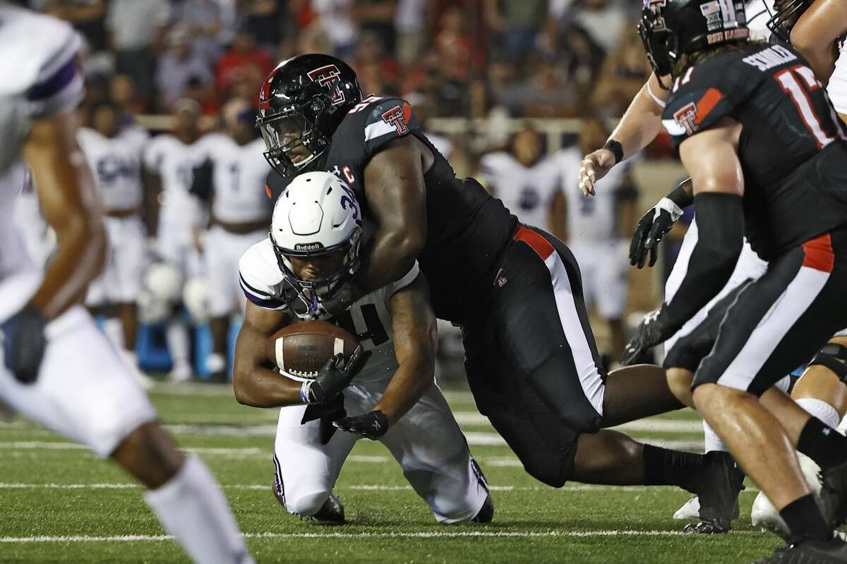 Texas Tech's Jaylon Hutchings tackles Stephen F. Austin's Ja'Bray Young (34) during the second half of an NCAA college football game Saturday, Sept. 11, 2021, in Lubbock, Texas. (AP Photo/Brad Tollefson)