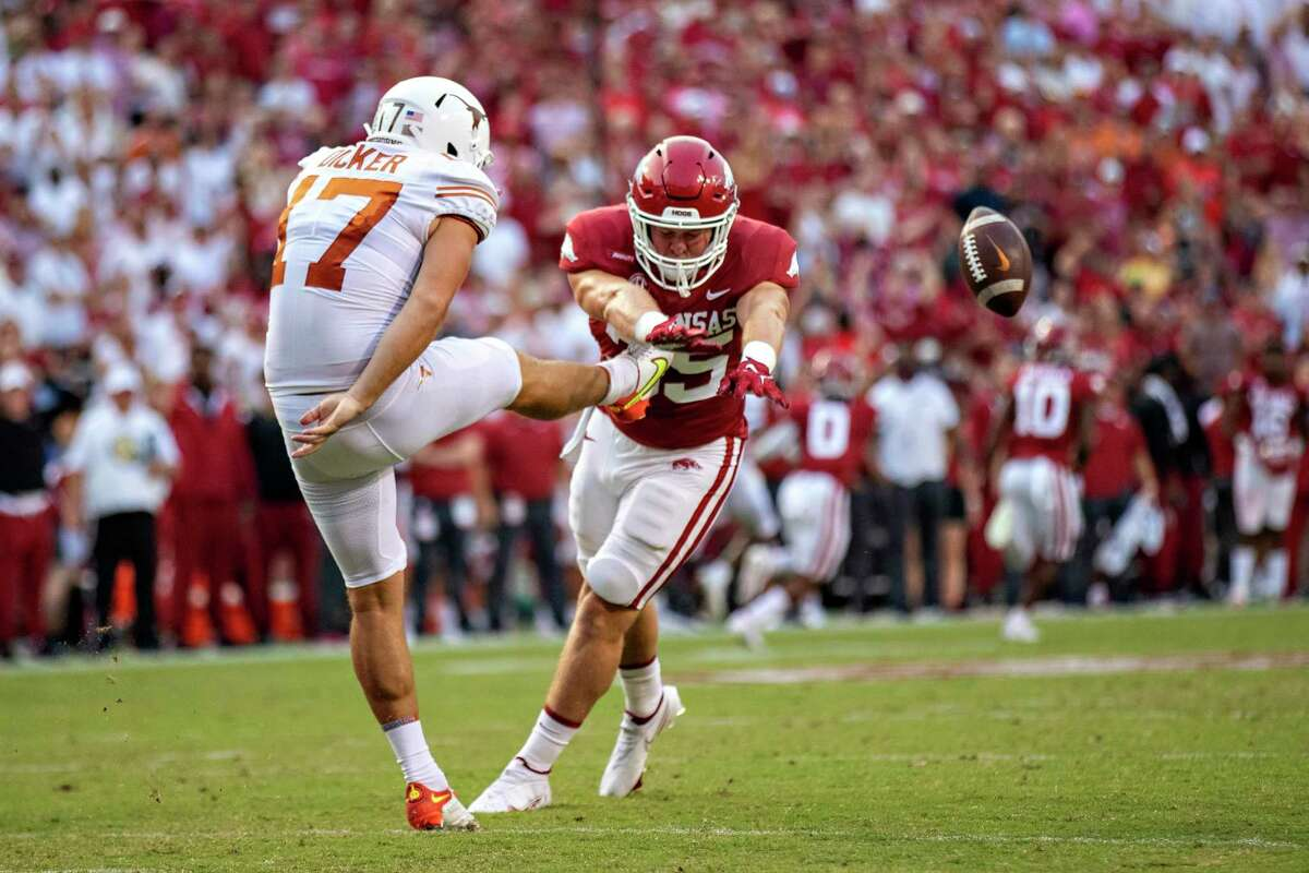 Cameron Dicker of Texas has his punt blocked in the first half by Jake Yurachek (25) of Arkansas during Saturday's game at Fayetteville.