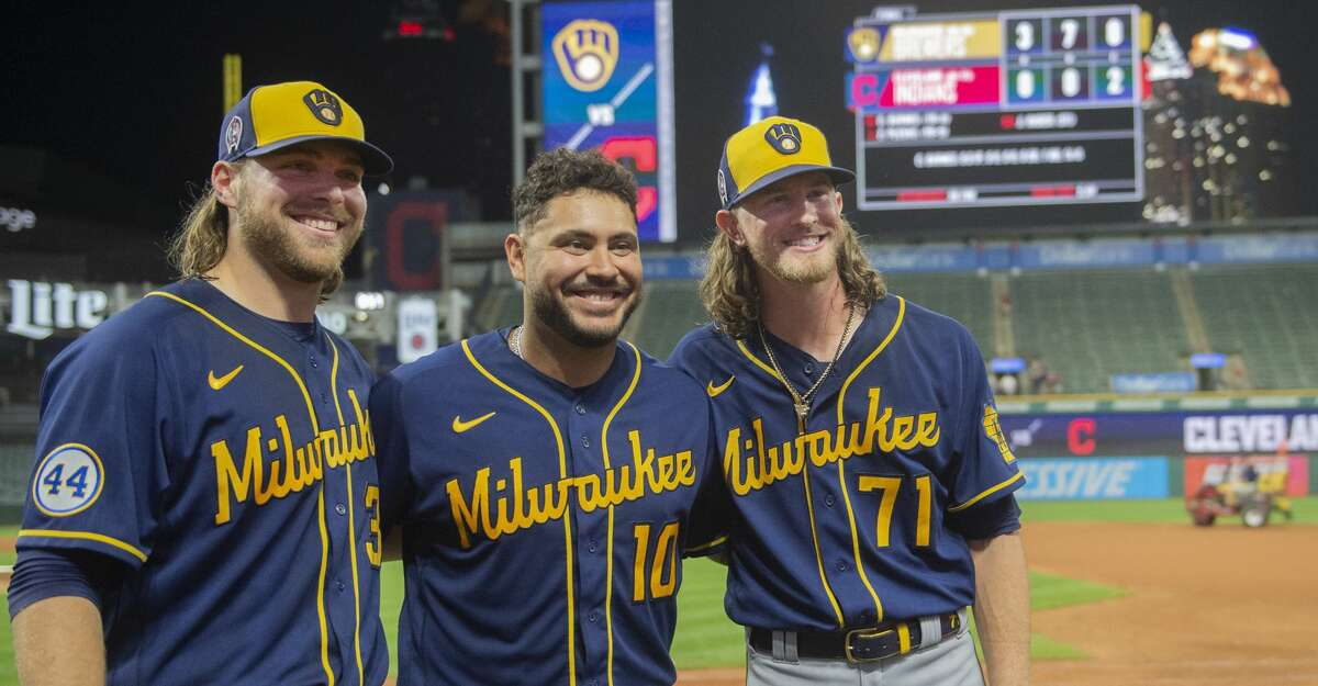 Milwaukee Brewers starter Corbin Burnes, left, poses with catcher Omar Narvaez, center, and reliever Josh Hader as they celebrate pitching a combined no-hitter against the Cleveland Indians at the end of a baseball game in Cleveland, Saturday, Sept. 11, 2021. (AP Photo/Phil Long)