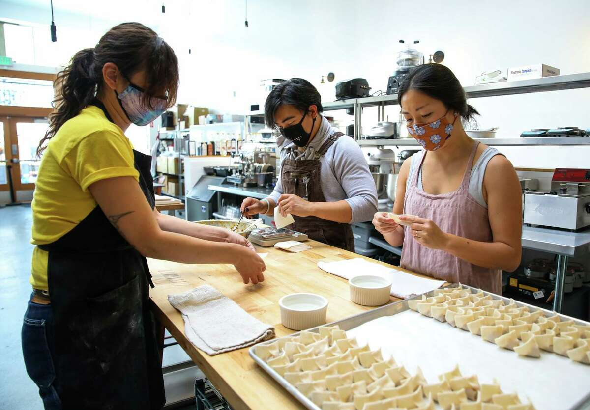 Nikki Munoz (left), Htet and Cathay Bi, owner of Dumpling Club, work in a commercial kitchen in San Francisco. Bi closed the business in August to give herself and her staff time off.