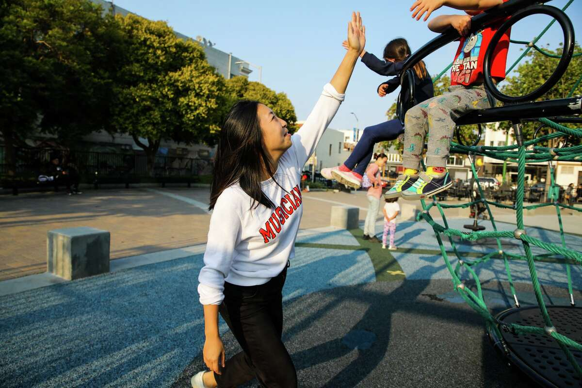 Dumpling Club owner Cathay Bi plays with her children at a playground in San Francisco. She's structured her business to keep boundaries around her personal life, especially so she can be present for her children.