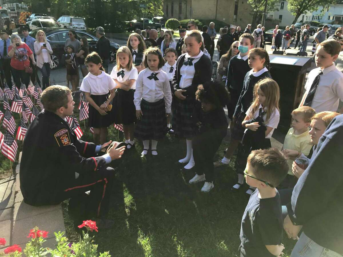 Torrington firefighter Timothy O'Donnell, seated left, explains events of Sept. 11, 2001, to students from St. John Paul the Great Academy at a ceremony at the North Firehouse on Main Street, Torrington, during the city's annual memorial ceremony.