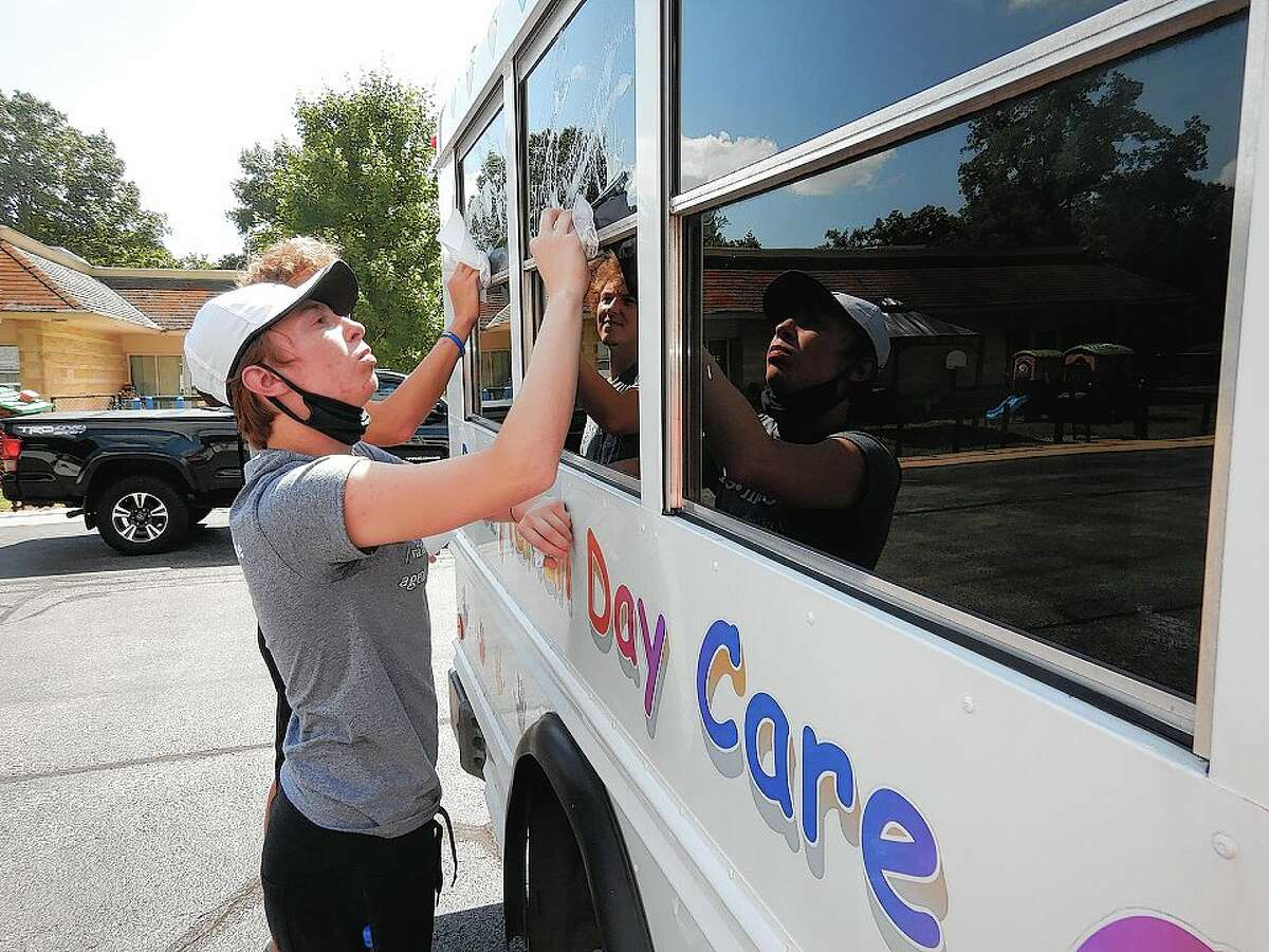 Alex Harden of Springfield cleans a daycare van during Illinois College's Day of Service.