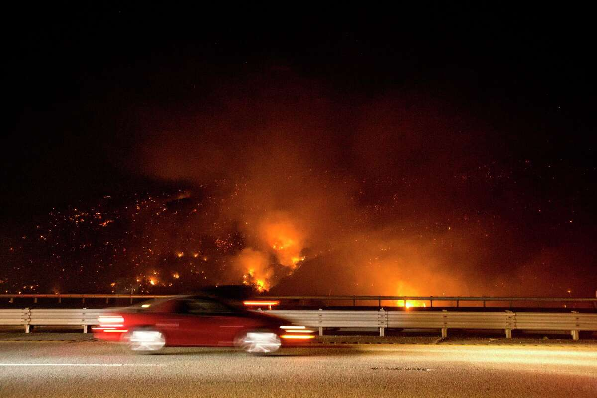 A vehicle passes by the burning Route fire, a brush wildfire off Interstate 5 north of Castaic, Calif., Saturday, Sept. 11, 2021. The wildfire near Castaic Saturday has led to the closure of a part of the major freeway in Southern California, officials told local media. (AP Photo/Ringo H.W. Chiu)