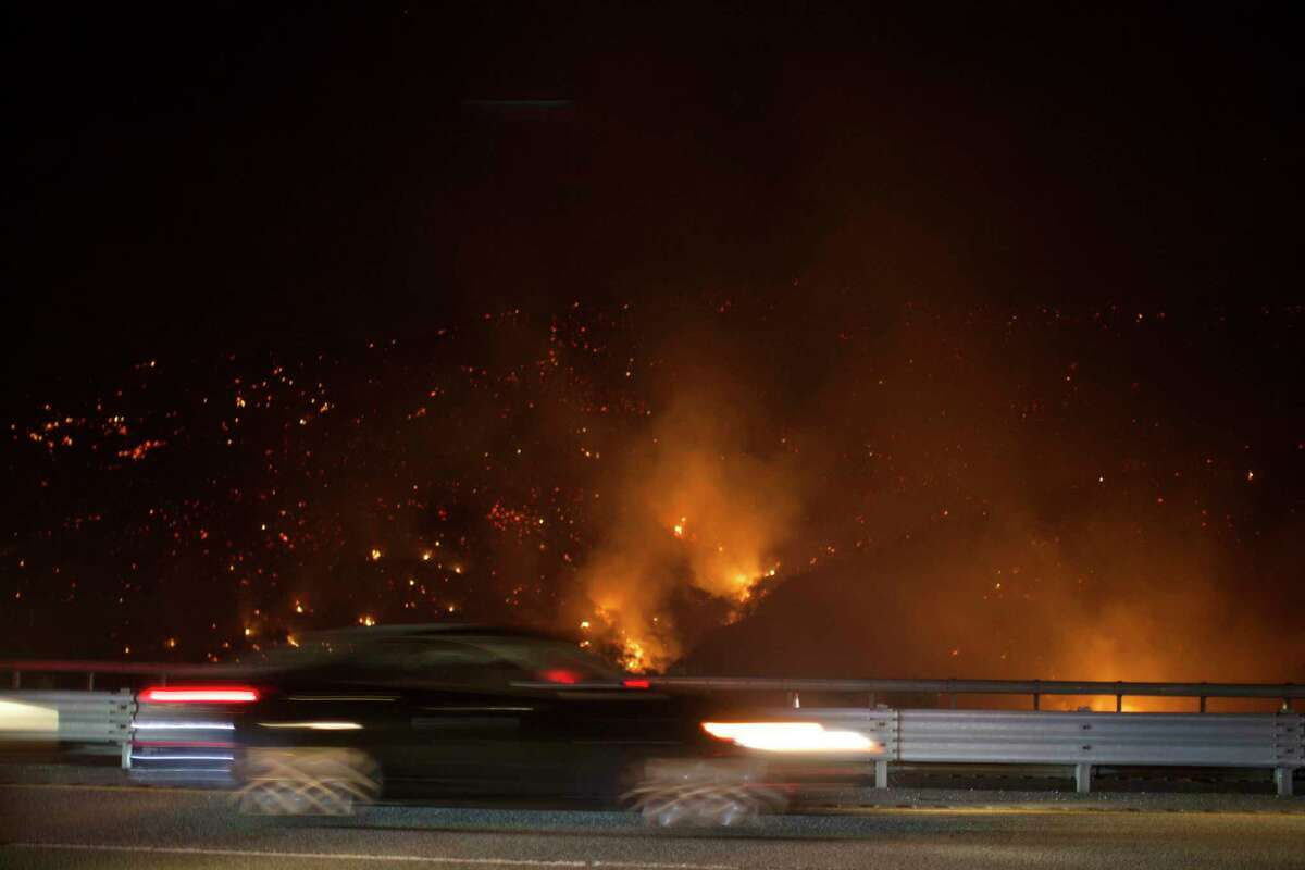 A vehicle drives on Interstate 5 south bound past the burning Route fire, a brush wildfire off Interstate 5 north of Castaic, Calif., on Saturday, Sept. 11, 2021. The wildfire near Castaic Saturday has led to the closure of a part of the major freeway in Southern California, officials told local media. (AP Photo/Ringo H.W. Chiu)