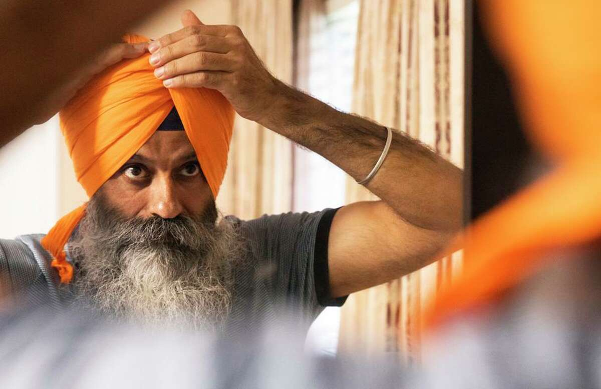 Taranjit Singh wraps his turban at his home in Fremont. There are an estimated 500,000 Sikhs in the U.S.