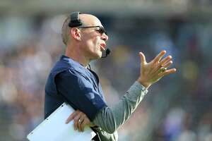 Connecticut interim head coach Lou Spanos gestures from the sideline during the first half of an NCAA football game against Purdue on Saturday, Sept. 11, 2021, in East Hartford, Conn. (AP Photo/Stew Milne)