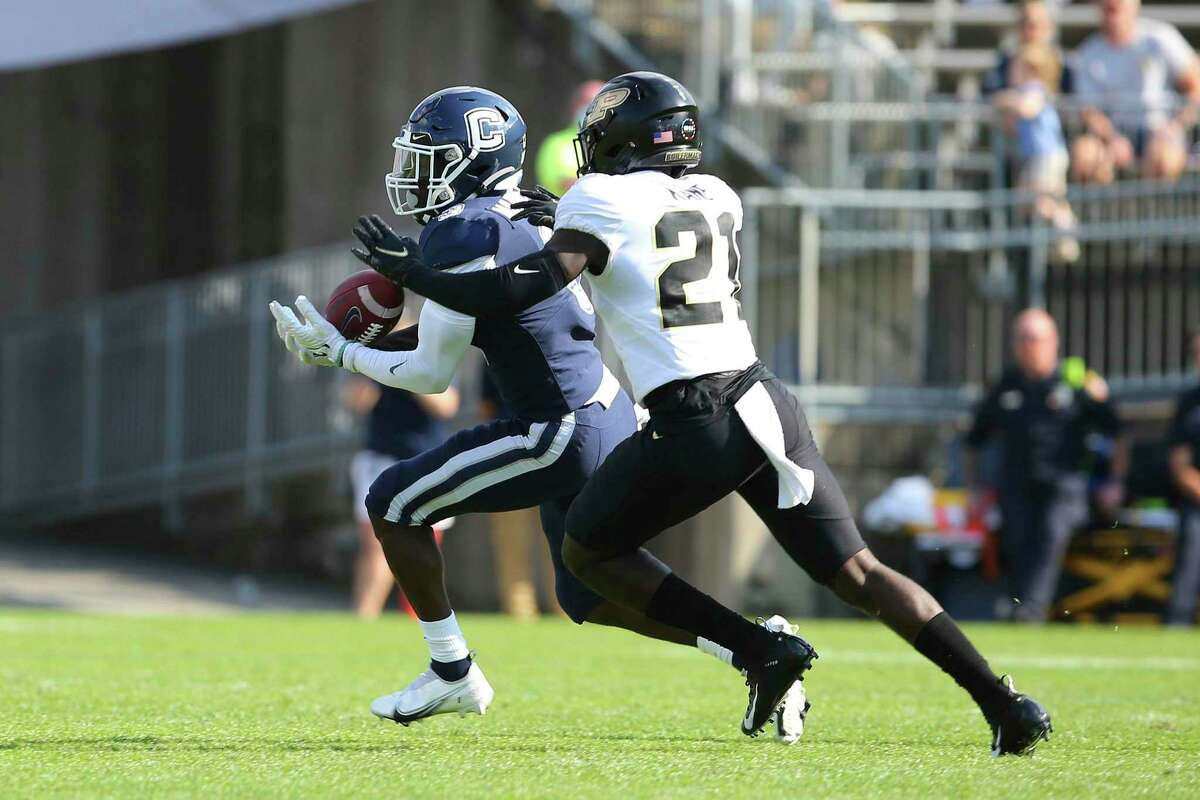 Connecticut wide receiver Heron Maurisseau (3) catches a pass as Purdue safety Sanoussi Kane (21) defends during the first half of an NCAA football game on Saturday, Sept. 11, 2021, in East Hartford, Conn. (AP Photo/Stew Milne)