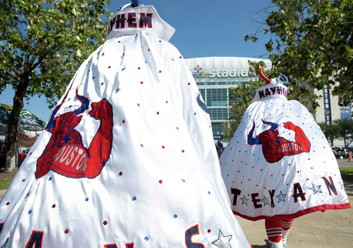 Houston Texans fans Roberto Doan, left, and Mauro Celestino, known as Masked Mayhem, walk toward the stadium before the NFL game against Jacksonville Jaguars Sunday, Sept. 12, 2021, at NRG Stadium parking lot in Houston.