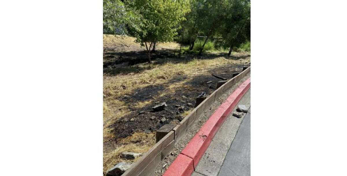 The ground is charred in a field where police say a man intentionally lighted a grass fire near a shopping mall in Santa Rosa on Saturday.