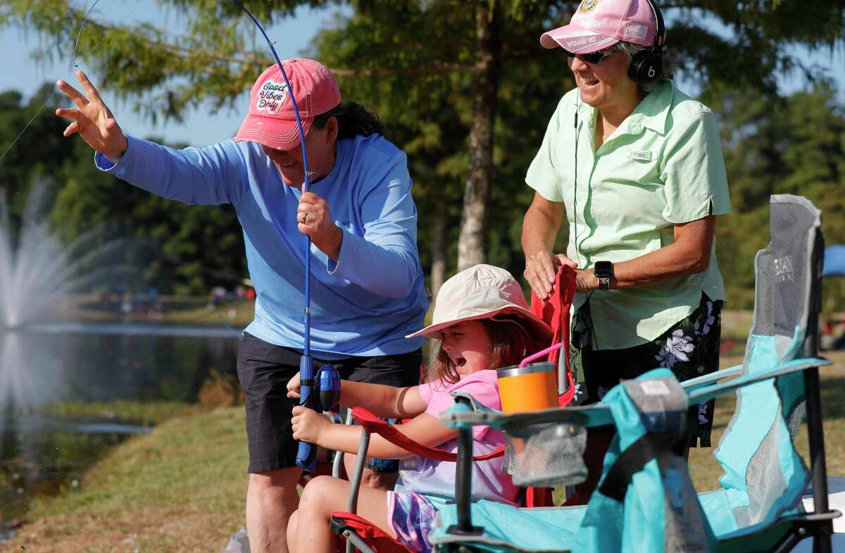 Elizabeth Poffinbarger, center reacts as she pulls in a catfish with the help of her grandmother, Shelia Thomas, and her wife, Heilda, during KidFish at Carl Barton, Jr. Park, Saturday, Sept. 11, 2021, in Conroe. The free event gave children 16 years old and young a chance to learn and gain appreciation for the sport of fishing as well as awareness for the environment.
