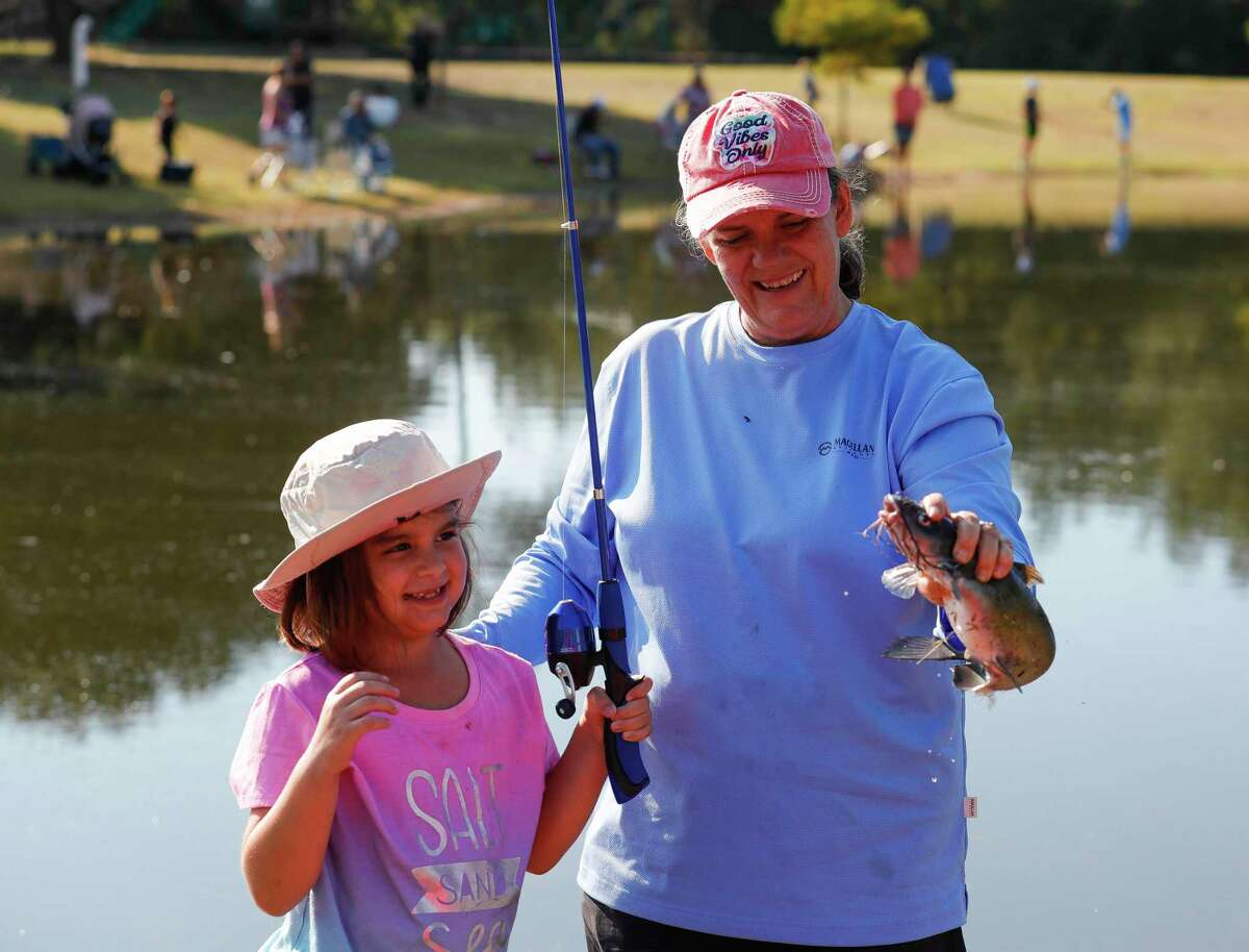 Elizabeth Poffinbarger, left, reacts after reeling in a catfish with the help of her grandmother, Shelia Thomas, during KidFish at Carl Barton, Jr. Park, Saturday, Sept. 11, 2021, in Conroe. The free event gave children 16 years old and young a chance to learn and gain appreciation for the sport of fishing as well as awareness for the environment.