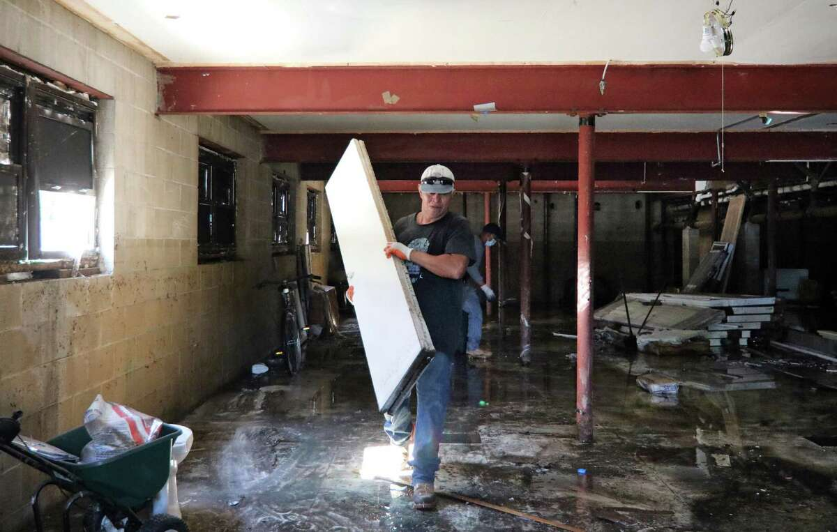 A worker removes destroyed items from the flooded basement at Cove Road Apartments in Stamford, Conn., on Tuesday Sentember 7, 2021. Remnants of Hurricae Ida last week caused damage to the apartments, forcing residents to find alternative housing.