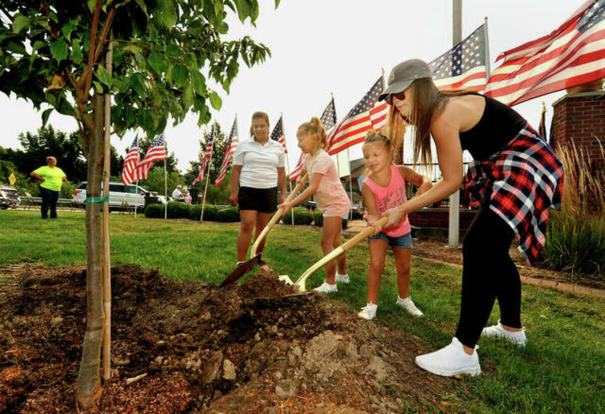 (from right to left) Kasey Patterson and her two daughters Ophelia, 5, and Sophia, 8, help plant trees as Glen Carbon committee member Abby Kansal watches. Tree planting, along with speakers, a firing squad and a moment of silence, took place during the ceremony Saturday.