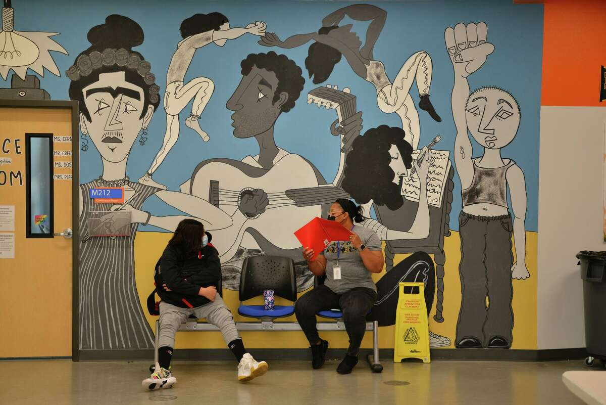 Siddhartha Hill and Quinetta Beard chat at KIPP Aspire Academy. The charter network requires all students and teachers to wear masks.
