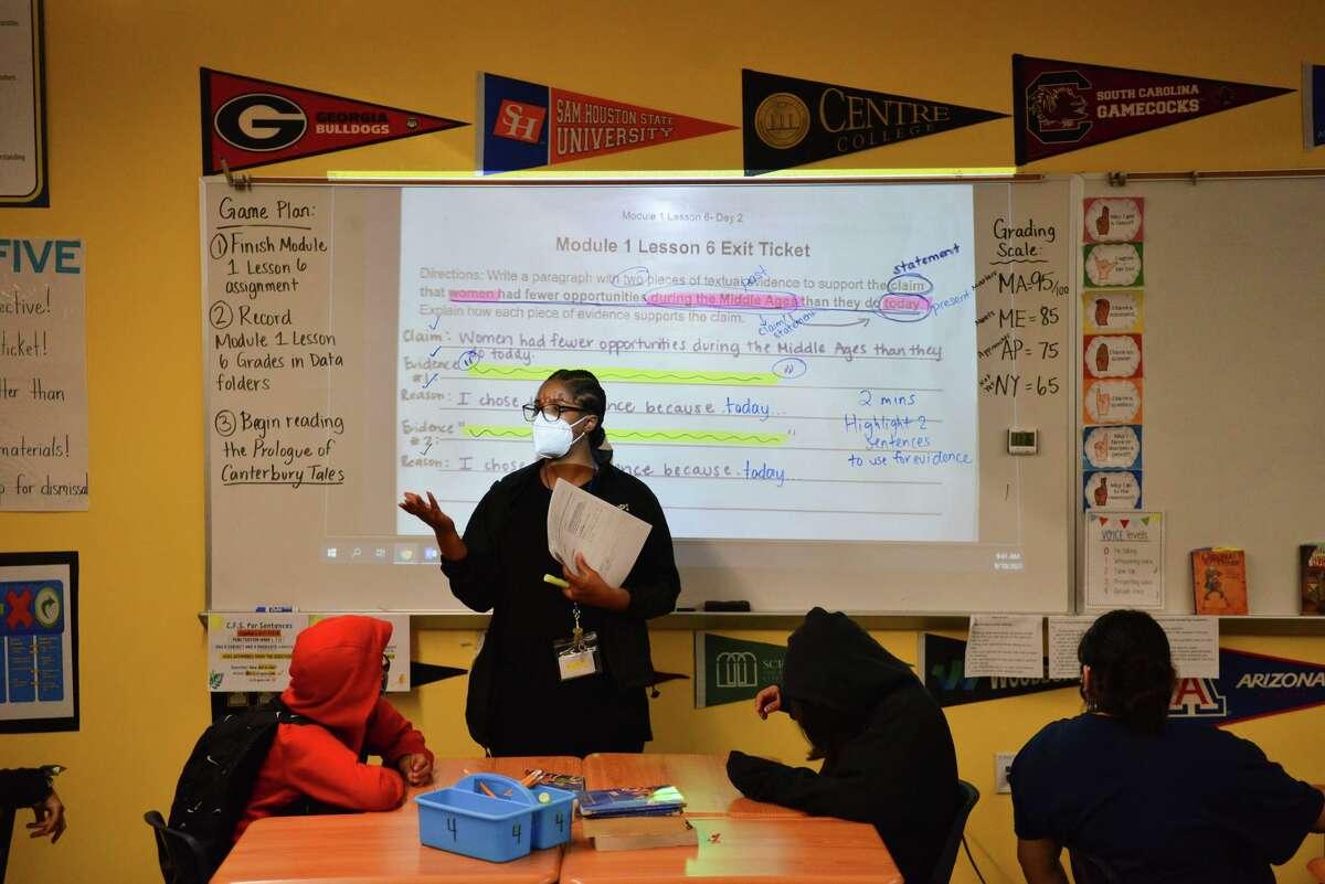 Teacher Neiya Nelson high fives a seventh grader at KIPP Aspire Academy. The charter network requires all students and teachers to wear masks.
