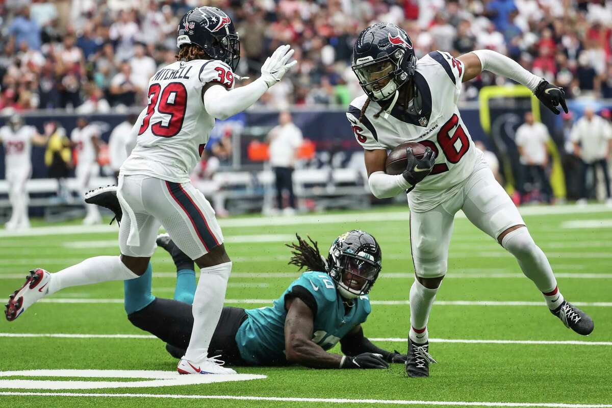 Houston Texans cornerback Vernon Hargreaves III (26) runs past Jacksonville Jaguars wide receiver Laviska Shenault Jr. (10) as a returns an interception of a Trevor Lawrence pass during the second quarter of an NFL football game Sunday, Sept. 12, 2021, in Houston.