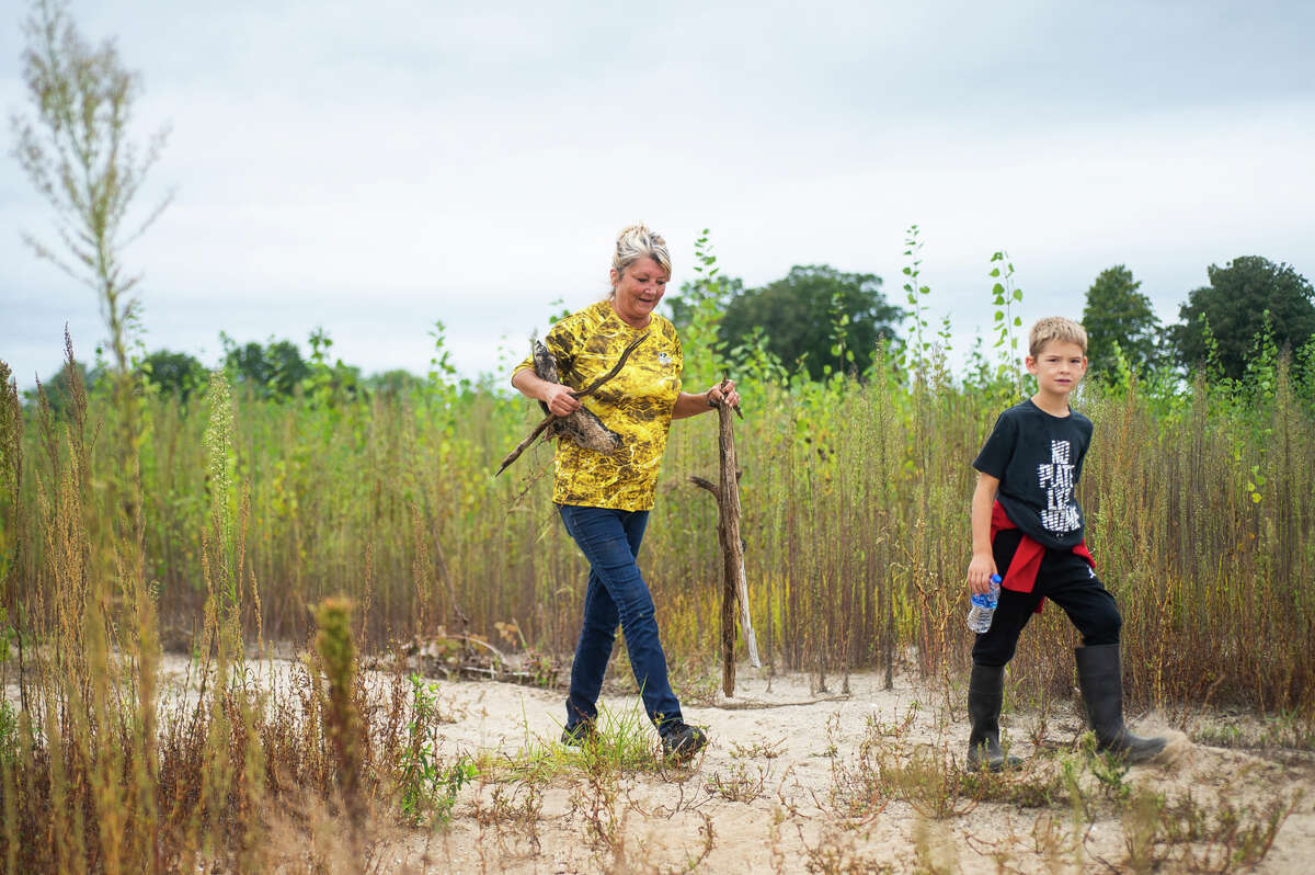 Debra Krzciok, center, and her grandson Tucker Judd, 6, right, work with dozens of other volunteers to remove debris from the Pontoon Alley area of Wixom Lake Sunday, Sept. 12, 2021 in Beaverton. (Katy Kildee/kkildee@mdn.net)