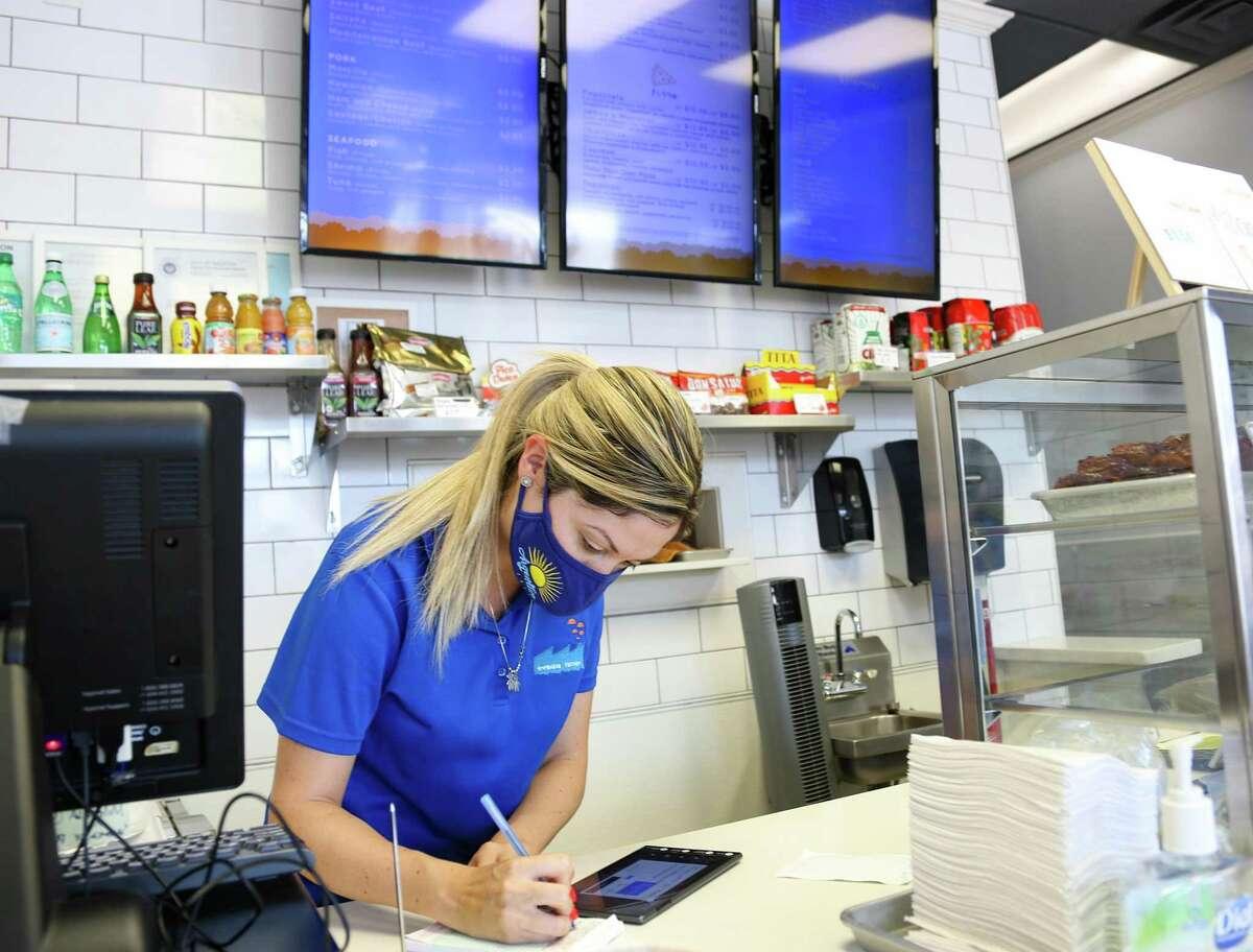 Greisy Perekalski, co-owner of Argentina Empanada Factory, takes an online order at the Houston restaurant on Tuesday, Aug. 10, 2021.