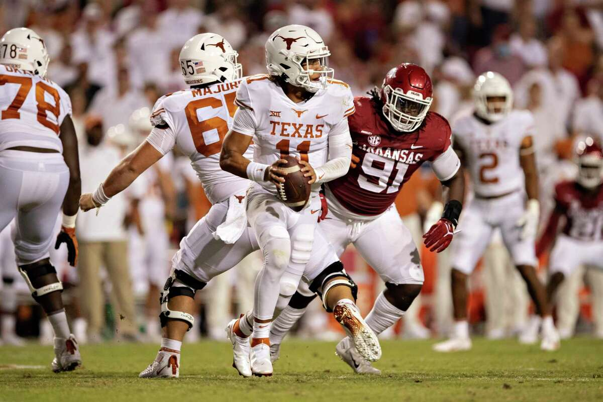Casey Thompson #11 of the Texas Longhorns rolls out looking for a receiver in the second half of a game against the Arkansas Razorbacks at Donald W. Reynolds Razorback Stadium on September 11, 2021 in Fayetteville, Arkansas. The Razorbacks defeated the Longhorns 40-21.