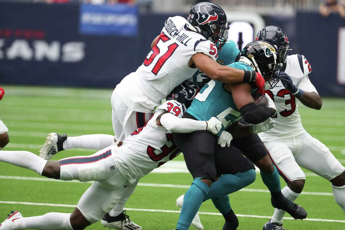 Jacksonville Jaguars running back James Robinson (25) is stopped by Houston Texans cornerback Terrance Mitchell (39) and Houston Texans linebacker Kamu Grugier-Hill (51) during the second quarter of an NFL football game Sunday, Sept. 12, 2021, in Houston.
