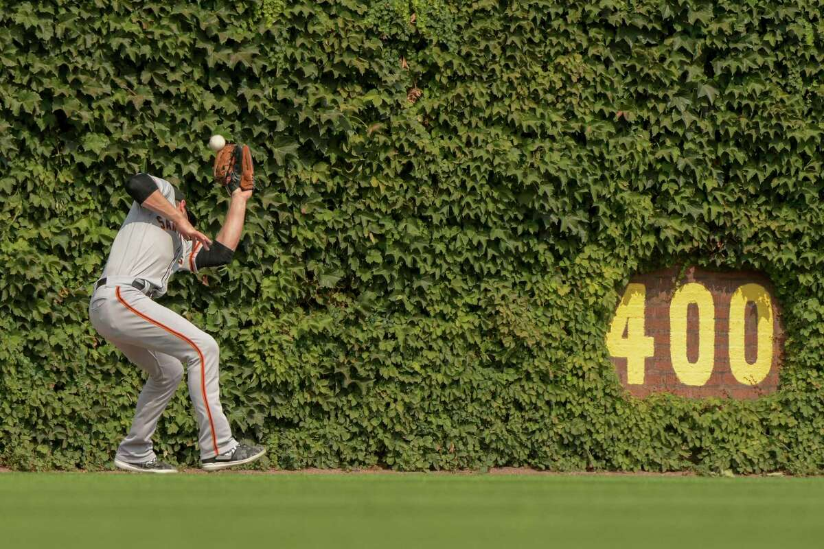 San Francisco Giants center fielder Austin Slater (13) drops a ball hit by Chicago Cubs Rafael Ortega during the fourth inning of a baseball game Sunday, Sept. 12, 2021, in Chicago. (AP Photo/Mark Black)