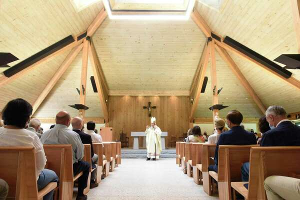 """Bishop Frank Caggiano leads Mass at St. Michael the Archangel Church in Greenwich, above, and blesses it with holy water, right, during a """"Mass of Dedication"""" at the newly renovated church Sunday."""