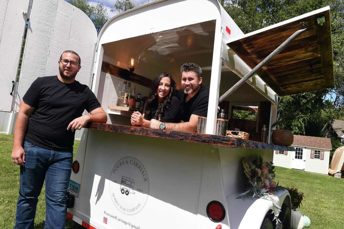 From left, Andrew Boyle, Nick Currie, his wife, Sarah, owners of the Pours & Carriage Mobile Bar Company, are photographed with the converted horse trailer in Orange on Sept. 10, 2021.