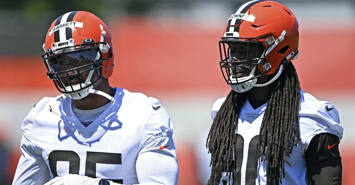 FILE - In this June 17, 2021, file photo, Cleveland Browns defensive linemen Jadeveon Clowney, right, and Myles Garrett watch during NFL football practice in Berea, Ohio. he Browns will have at least seven new starters on defense, maybe more depending on the package they're in, when the season kicks off Sunday against the Kansas City Chiefs at Arrowhead. (AP Photo/David Dermer, File)